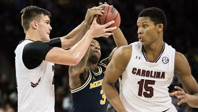Michigan guard Xavier Simpson (3) and South Carolina forward Maik Kotsar, left, battle for a loose ball during the first half of an NCAA college basketball game Wednesday, Nov. 23, 2016, in Columbia, S.C.