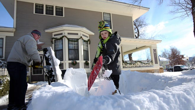 Kadin Viers, 10, receives help from his grandpa, Mike Bacon, while building a snow fort on  Dec. 22 in Hutchinson, Kan.