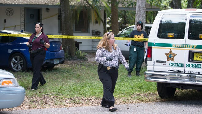 Lee County Sheriff detectives and crime scene technicians work outside a home on LaBelle Avenue in Tice on Thursday.