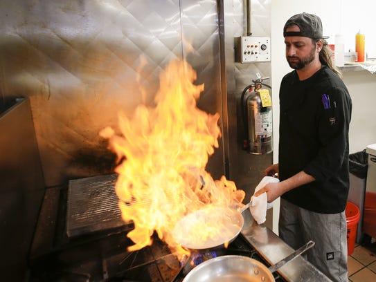 EnVie chef and co-owner James Cheskaty flambés diver
