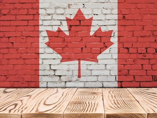 Canada flag painted on brick wall with wooden floor