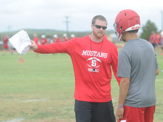 First-year Sweetwater coach Ben McGehee, left, talks to a player during the Mustangs first day of fall practice Monday, Aug. 7, 2017 in Sweetwater.