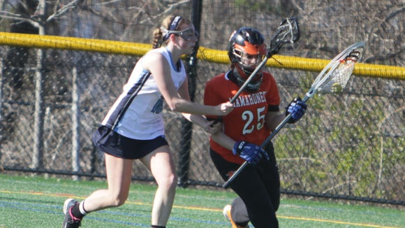 Mamaroneck goalie Talia Land is defended by Ursuline's Madison Boutureira during a Section 1 girls lacrosse game between Ursuline and Mamaroneck at the Ursuline School on Thursday, April 14th, 2016. Mamaroneck won 12-10.