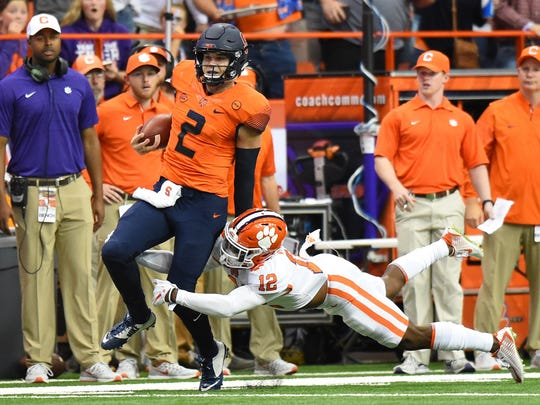 Syracuse quarterback Eric Dungey (2) tries to elude Clemson defender K'Von Wallace (12) during the third quarter in Syracuse, N.Y.  Dungey threw three TD passes to lead the Orange to a 27-24 upset of the No. 2 Tigers.