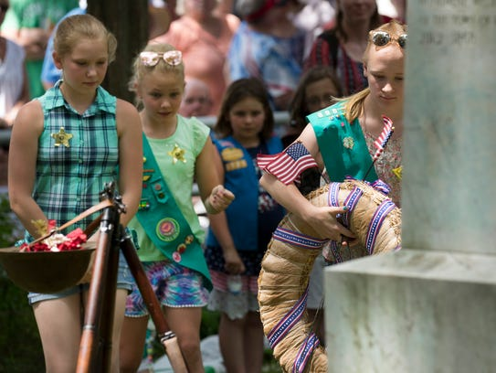 Girl Scouts place a wreath at a monument erected to the Civil War dead during the Town of Rhine's Memorial Day observance and picnic Monday.