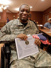 """Kevin Lee smiles as he receives his certificate of service when Seasons Hospice & Palliative Care organized a  """"We Honor Veterans"""" day to give pins and certificates to veterans they are caring for at The Villa at Bradley Estates."""