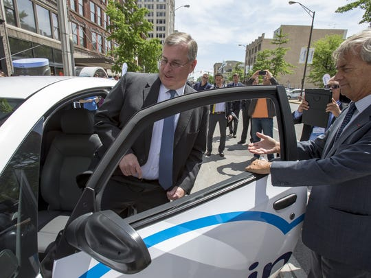 Vincent Bollor, CEO of investment group Bollor, opens the door on one of the new BlueIndy cars for Mayor Greg Ballard, at a ribbon cutting for the new car share program that will give residents an opportunity to rent inexpensive electric cars for short local trips