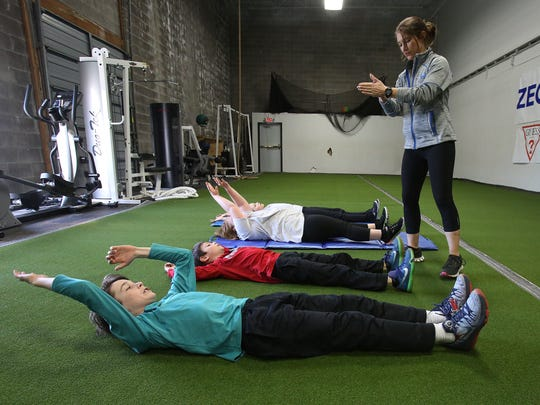 Exercise physiologist Missy Sachs, right, has students perform abdominal exercises during a prime class at the Louisville Youth Training Center.  Mar. 22, 2016