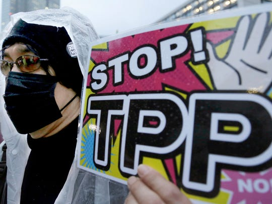 In this April 22, 2014 file photo, a protester holds a placard during a rally against the Trans-Pacific Partnership (TPP) in Tokyo. Donald Trump and Hillary Clinton agree on almost nothing, except for their dislike of a sweeping agreement that would erase most tariffs and other trade barriers among the U.S. and 11 other nations. All the bashing from the presidential candidates has created more difficulties for the Trans-Pacific Partnership, one of President Barack Obama''s top priorities in his final year in office.