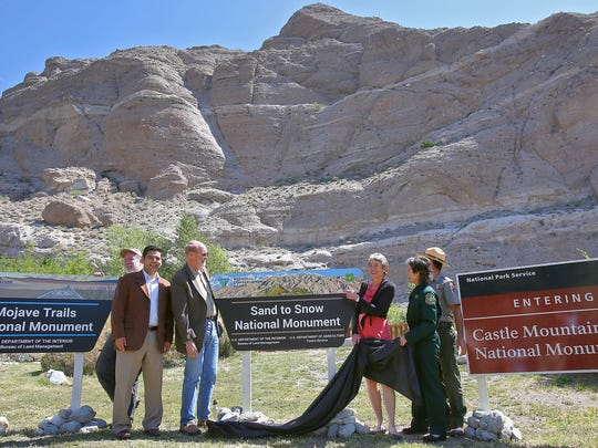 Officials unveil three signs advertising the California desert's new national monuments during a celebration at the Whitewater Preserve on May 5, 2016.  From left, in foreground, are Rep. Raul Ruiz, Wildlands Conservancy Executive Director David Myers, Interior Secretary Sally Jewell and Jody Noiron, supervisor of the San Bernardino National Forest.
