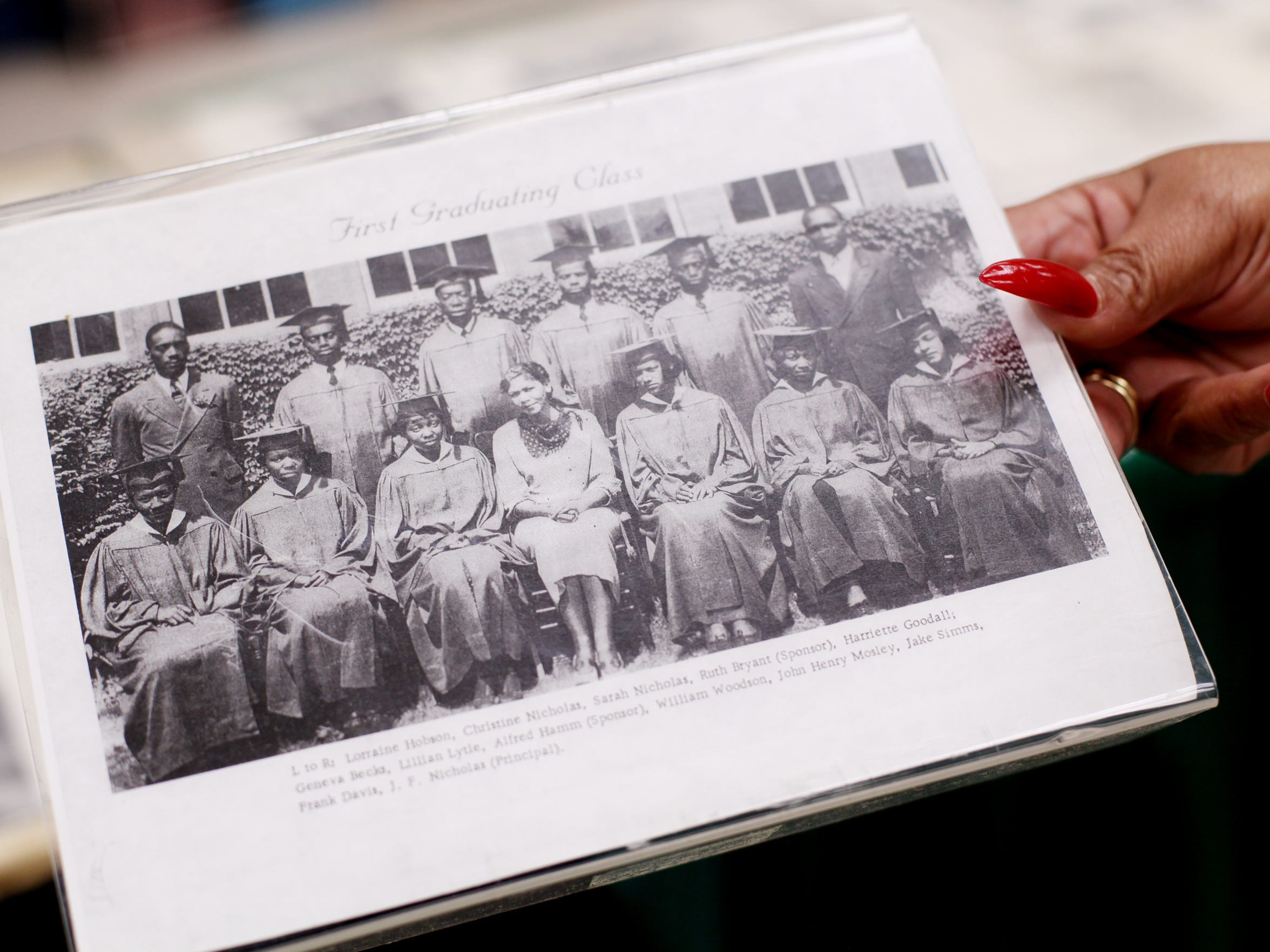 Nita Bellamy holds a photo of the first graduating