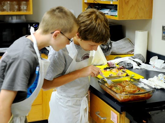 Dalton Kuhn (right) and Derek Hollinger check to see if their Alvondigas's (Spanish meatballs) are done in the center during their cooking class Delicioso! at Super Summer Camp at USI in 2015.
