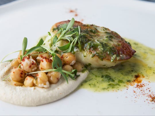 Chermoula-seared cod is served with hummus, marinated