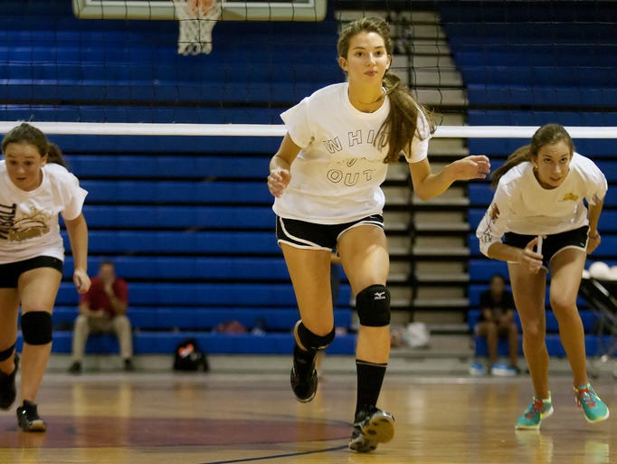 Southwest Florida Christian Academy's Nicole Nicely, 17, center, leads a volleyball conditioning drill during practice Friday at SFCA in Fort Myers.