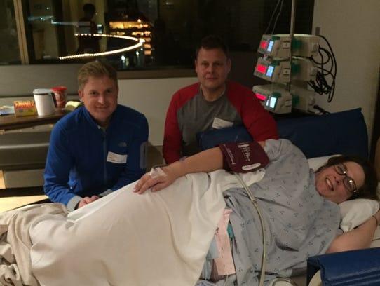 Dana Hawkins, on bed, Chad Waltz and his husband, shown