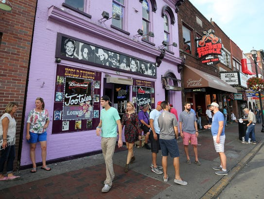 Visitors to Lower Broad make their way past Tootsies