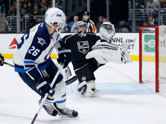 Winnipeg Jets right wing Blake Wheeler, left, watches as he misses a shot-attempt while Los Angeles Kings goalie Jonathan Quick, right, protects the net during the first period of an NHL hockey game, Saturday, April 9, 2016, in Los Angeles. (AP Photo/Danny Moloshok)