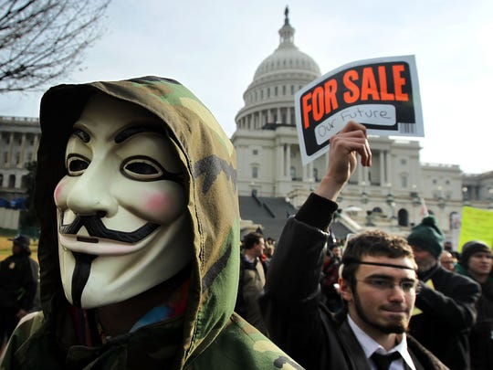 "A demonstrator wears a Guy Fawkes mask during an ""Occupy"