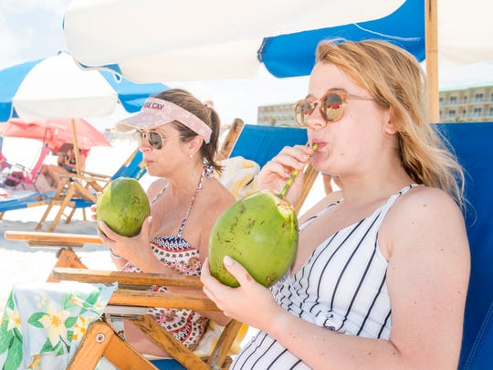 Lorri Wickam, left, and her daughter Mallory Wickam, of Cleveland, Tennessee, enjoy drinking fresh, chilled coconut water from Florida Coconuts while sitting along Pensacola Beach. A more adult version could be filling a honey dew melon with rum or a watermelon with vodka.