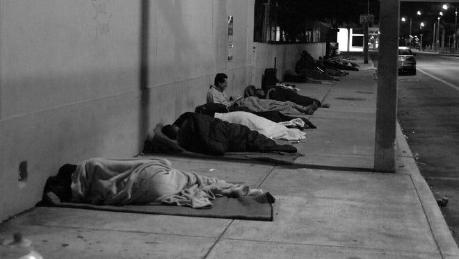 Homeless persons sleep on the sidewalk.