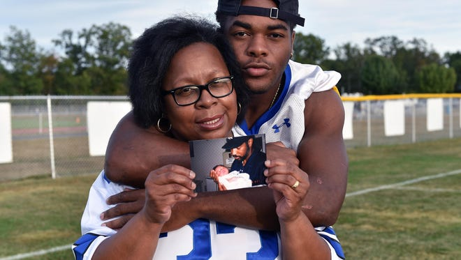 Buena's football player, Sam Crouch along with his mother, Pam Crouch, who holds a picture of her son Sam being held by his late father Michael Crouch when he was a baby.  Sam's father passed away in 2013 also wore #33 and played for Buena.  Sept. 24, 2015