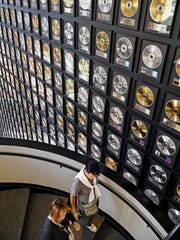 Visitors make their way past a wall of gold records as they descend the stairs at the Country Music Hall of Fame and Museum Aug. 9, 2017.