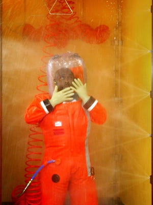 A CDC microbiologist wearing a full-body positive-pressure suit undergoes a decontamination shower before exiting a biosafety  level 4 lab at the Centers for Disease Control and Prevention in Atlanta. The process involved a four-minute chemical shower followed by a three-minute rinse with water, according to the CDC.