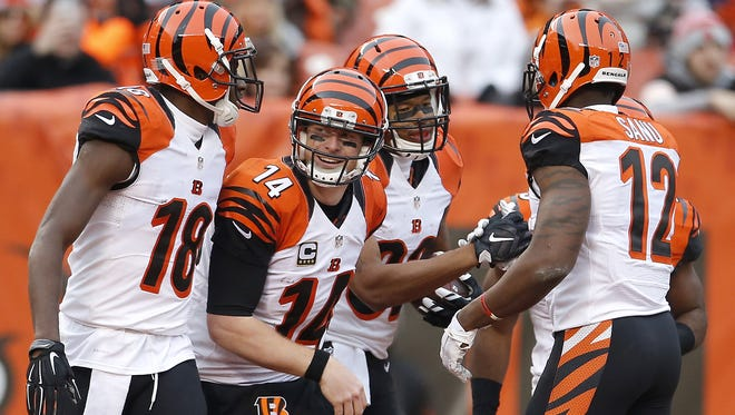 Cincinnati Bengals quarterback Andy Dalton (14), center, smiles after Cincinnati Bengals wide receiver Marvin Jones (82) scored a touchdown in the third quarter during the Week 13 NFL game between the Cincinnati Bengals and the Cleveland Browns, Sunday, Dec. 6, 2015, at FirstEnergy Stadium in Cleveland. The Bengals won 37-3.