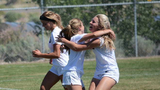 Aztec's Kortney Horn, center, celebrates a goal scored by teammate Autumn Roundy, right, during a nondistrict match against Hope Christian on Aug. 26. The Lady Tigers will open the 2018 season at home against Miyamura on Aug. 24.
