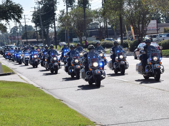 A motorcycle procession of law enforcement officers precedes the hearse carrying  Louisiana State Police trooper Bobby Smith as the funeral proceeds down Jackson Street Thursday after funeral services at Calvary Baptist Church in Alexandria.