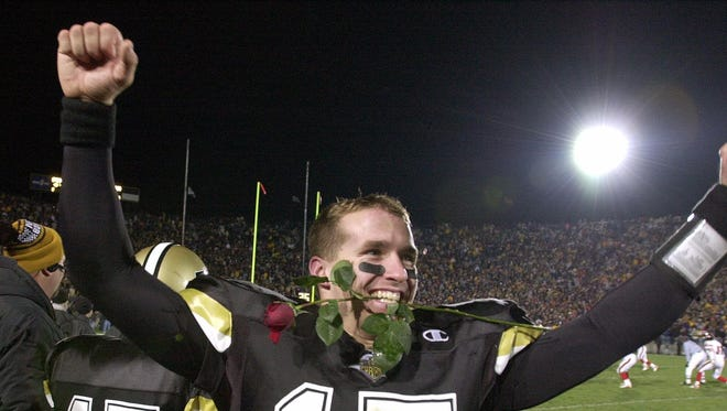 Purdue's Drew Brees, clenches a rose in his teeth as he celebrates Purdue's 43-14 victory over Indiana, Nov. 18, 2000. The win earned Purdue an invitation to the Rose Bowl.