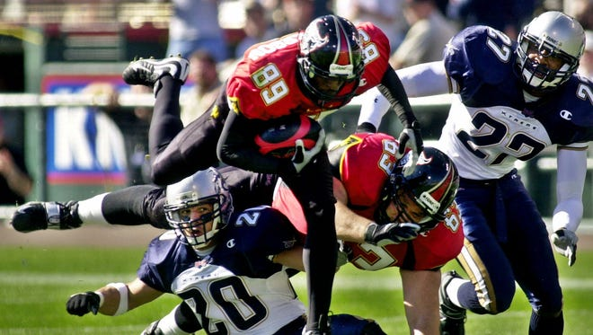 San Francisco Demons wide receiver Brian Roberson (89) jumps over Los Angeles Xtreme safety Jeff Russell (20) and teammate center Michael Kiselak as Xtreme safety Eric Johnson , right, looks on, right, for a 17 yard run during the first quarter, Sunday, Feb. 4, 2001 in San Francisco in their first XFL game. (AP Photo/Paul Sakuma)