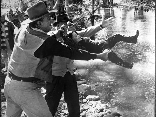 Not so fast! John Wayne pretends to toss son Ethan