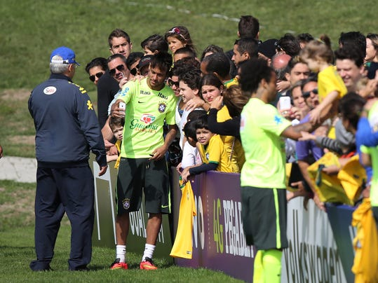 Brazil's palyer Neymar does a selfie with fans after a practice session at the Granja Comary training center in Teresopolis, Brazil, Sunday, June 1, 2014. Brazil's team will travel this Sunday for the team's warm-up against Panama on Tuesday in preparation for the World Cup soccer tournament that starts on 12 June. (AP Photo/Leo Correa)