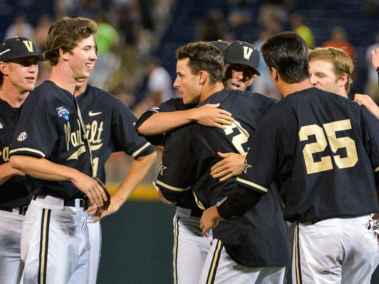 Vanderbilt players surround Tyler Campbell (2) who hit a single in the 10th inning that scored Rhett Wiseman for a 4-3 win over Texas in an NCAA baseball College World Series game in Omaha, Neb., Saturday, June 21, 2014. Vanderbilt advanced to the championship series. (AP Photo/Ted Kirk)