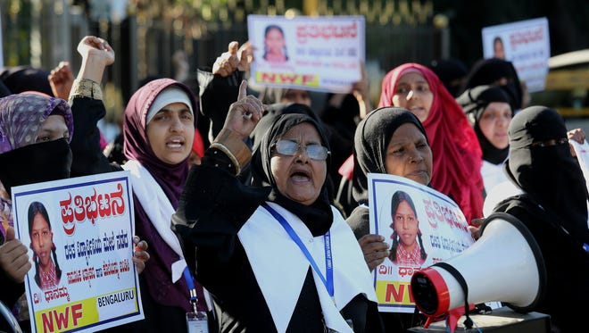 Members of National Women Front (NWF), a non-governmental organization, hold placards and shout slogans during a protest against the gang rape and murder of minor girl in North Karnataka, Bangalore, India, on Dec. 23, 2017.