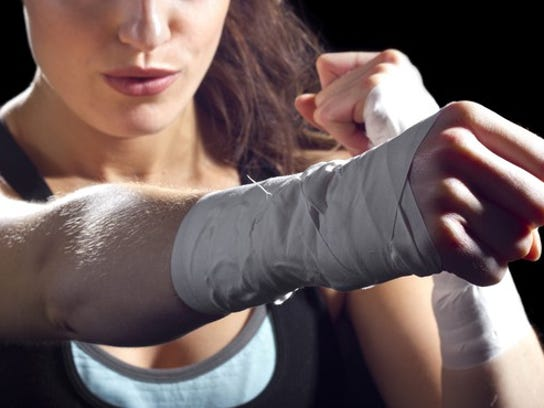 close up of woman with taped wrists defending herself and throwing a punch