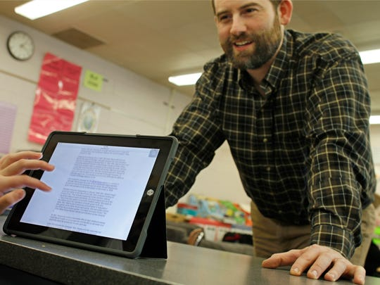 Fifth-grade teacher Michael Sereno works with his students on a reading project using school provided iPads at the Laurelton Pardee Intermediate School in East Irondequoit on Feb. 4.