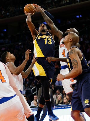 Indiana Pacers' Paul George (13) drives past New York Knicks' Ricky Ledo, left, and Quincy Acy, right, during the second half of an NBA basketball game Wednesday, April 8, 2015, in New York. (AP Photo/Frank Franklin II)