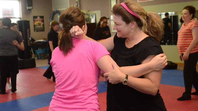 Virginia Norman (right) practices a defensive move on Brittany Dowden at a free self-defense class at Master Rousseau's Taekwondo Saturday. Carol Rousseau, senior master, was teaching the free class in honor of Mother's Day. Dowden attended the class with her mother Joyce Counts and Whitney Counts.