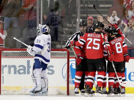 New Jersey Devils players, right, celebrate a goal by Drew Stafford (18) as Tampa Bay Lightning goalie Peter Budaj, of Slovakia, (31) composes himself during the first period of an NHL hockey game, Tuesday, Oct. 17, 2017, in Newark, N.J. (AP Photo/Julio Cortez)