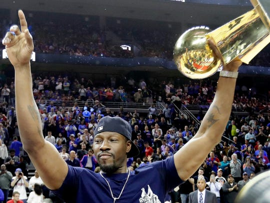 Former Pistons center Ben Wallace raises the Larry O'Brien NBA Championship Trophy won by the Pistons in 2004 during a halftime ceremony April 10, 2017 in Auburn Hills. This was the last Pistons game at the Palace.