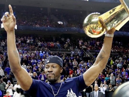 Former Pistons center Ben Wallace raises the Larry