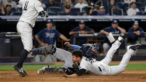 New York Yankees' Jacoby Ellsbury slides under the tag from Tampa Bay Rays catcher Curt Casali (19) to steal home as New York Yankees' Brett Gardner (11) steps out of the way in the fifth inning of a baseball game, Friday, April 22, 2016, in New York.