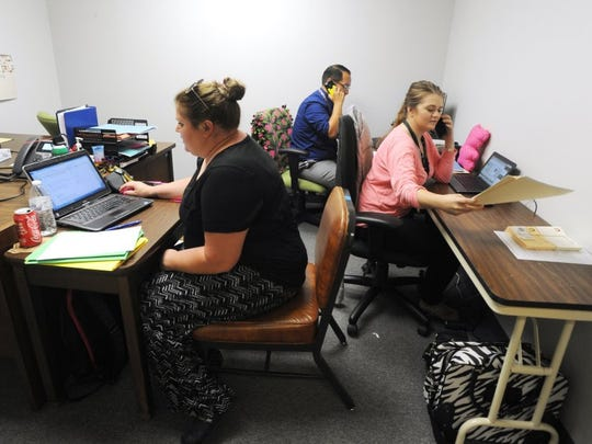 From left, investigation case workers Ashley McNally, Anthony Dela Garza, and Julie Reed share an office at Child Protective Services on Aug. 11.