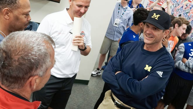 Michigan football coach Jim Harbaugh, right, and Ohio State's Urban Meyer, top center.