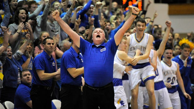 Castle head coach Brian Gibson (center) celebrates with his team as the Knights defeat New Albany 72-64 on Saturday in the 2017 IHSAA 4A Regional Basketball Final at Seymour High School. (Photo by David Lee Hartlage, Special to The Courier-Journal) Mar. 11, 2017