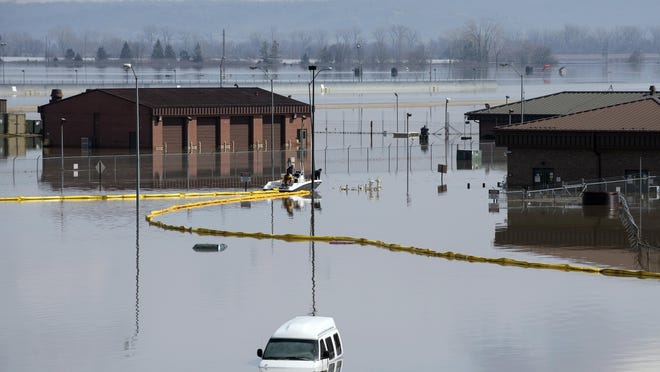 In this March 18, 2019 photo released by the U.S. Air Force, environmental restoration employees deploy a containment boom from a boat on Offutt Air Force Base in Neb., as a precautionary measure for possible fuel leaks in the flooded area.