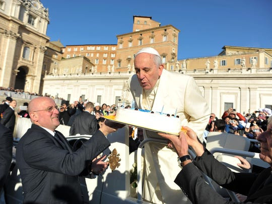 This handout picture released on December 17, 2014 by the Vatican press office shows Pope Francis blowing the candles of a birthday cake to celebrate his 78th birthday during a general audience at the Vatican.