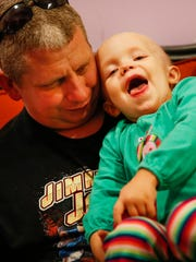 Kaydence Weaver, 2, who is suffering from a childhood cancer, laughs while sitting on the lap of her uncle and guardian Brandy Maddux at The Ronald McDonald House on Sept. 19, 2016. Weaver has been in treatment at Riley Hospital and Peyton Manning Children's Hospital.